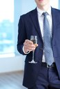 Corporate event close up of businessman in suit holding flute of champagne in hand Stock Images