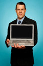 Corporate executive showing laptop to you Stock Photography