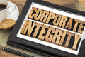 Corporate integrity on digital tablet business ethics concept text in letterpress wood type computer with stylus pen coffee cup Royalty Free Stock Photos