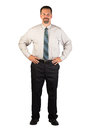 Corporate man standing with hands on hips a white collar worker facing the viewer firmly this could be a spokesperson for a Royalty Free Stock Photo