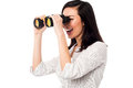 Corporate woman viewing through binoculars young businesswoman keeping an eye on her team from distance Royalty Free Stock Photography