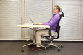 Correct sitting position at workstation man on chair working with laptop profile view Royalty Free Stock Images