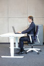 correct sitting position at workstation - man in suit - Royalty Free Stock Photo