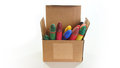 Corrugated cardboard box open with crayons inside on white background Royalty Free Stock Photo