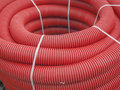 Corrugated pipe, drainage. In the roll, close-up. The tube is corrugated, red. Royalty Free Stock Photo