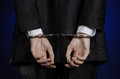 Corruption and bribery theme: businessman in a black suit with handcuffs on his hands on a dark blue background in studio isolated Royalty Free Stock Photo