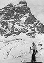 Cortina, Italy - 1939 Skier resting and smiling with Dolomites m Royalty Free Stock Photo