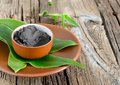 Cosmetic clay in a ceramic bowl decorated with fresh green leaves spa body and face treatment Royalty Free Stock Photos