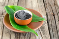 Cosmetic clay in a ceramic bowl decorated with fresh green leaves spa body and face treatment Royalty Free Stock Image