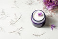 Cosmetic cream and lavender flowers on white wood table background Royalty Free Stock Photo