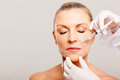Cosmetic injection to mature woman face Royalty Free Stock Image