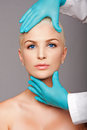 Cosmetic plastic surgeon touching aesthetics face Royalty Free Stock Photo