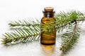 Cosmetic spruce oil in bottles with fur branches on white table background Royalty Free Stock Photo