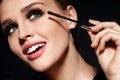 Cosmetics. Beautiful Woman With Perfect Makeup Applying Mascara Royalty Free Stock Photo