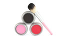 Cosmetics a blush brush and three different colors of makeup Stock Image