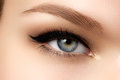 Cosmetics make up beautiful female eye with sexy black liner makeup fashion big arrow shape on woman s eyelid chic evening Royalty Free Stock Image