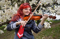 Cosplayer playing the violin a happy teenage girl is in flowering garden she is wearing an anime costume and a wig Royalty Free Stock Photo