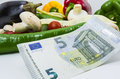 Cost of food concept five euro banknote and vegetables on white background Royalty Free Stock Image