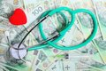 Cost of health care stethoscope red heart polish money medical treatment and high for a good service concept zloty paper banknotes Royalty Free Stock Images