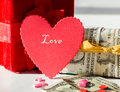 The cost of love a red heart and a read gift box with another box wrapped in money and bills and candy in foreground Royalty Free Stock Photography