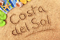 Costa del sol the words written on a sandy beach with beach towel starfish and flip flops Stock Images