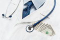 Costly health closeup of doctor s coat with money in the pocket symbolizing healthcare or corruption Royalty Free Stock Images