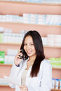 Costumer service executive using phone in pharmacy woman and holding prescription paper Royalty Free Stock Image