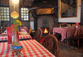Cosy fire restaurant photo of a kent with pink gingham covered tables and a real burning in the background Royalty Free Stock Images