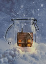 Cosy home country cottage in snow filled glass jar at night Royalty Free Stock Photo