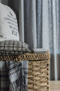 Cosy interior with wicker basket and woolen plaid and postcards in grey tones slogan on the pillow Royalty Free Stock Photos