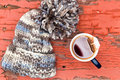 Cosy winter hat with a cup of fresh hot tea view from above cozy knitted woolly large pompom beside on grungy wooden surface Stock Image