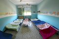 Cots with blankets for children in the nursery dormitory small kindergarten Royalty Free Stock Photos