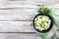 Cottage cheese with chives in black ceramic bowl on rustic woode