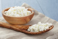 Cottage cheese in wood bowl on blue wooden table Royalty Free Stock Photo