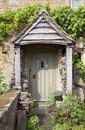 Cottage door with flowers pretty english doorway logs and cotswolds gloucestershire england Stock Images