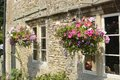 Cottage with hanging flower baskets wiltshire england stone in front of windows Stock Images