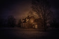 Cottage in the snow with light in the window Royalty Free Stock Photo