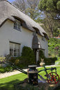 Cottage Thatched con il bidone da latte decorato Immagine Stock