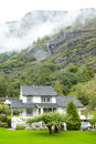 Cottages in mountains, waterfall and mist. Royalty Free Stock Photos