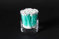 Cotton swabs in clear glass jar on black background turquoise Stock Photos