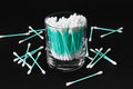 Cotton swabs in clear glass jar on black background turquoise Royalty Free Stock Photography