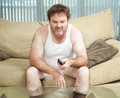 Couch potato watching tv unemployed man sitting home bored and discouraged Stock Photography