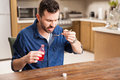 Cough syrup is disgusting young man having trouble to drink some at home Stock Photos
