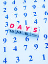 Counting the days text in red uppercase letters on small white cubes placed upon an array of numbers in blue making concept of Stock Photography