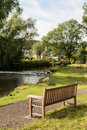 Country bench rustic overlooking stream of water in bakewell derbyshire uk Royalty Free Stock Photos