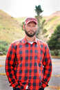 Country boy closeup of a somber unshaven or labor worker with red plaid shirt and ball cap on shallow depth of field Royalty Free Stock Images