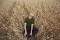 Country boy in wheat field a handsome young with straw hat on sitting a golden Stock Image