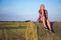Country concept young woman sitting on haystack in field beautiful Royalty Free Stock Photos