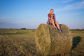 Country concept young woman sitting on haystack over blue sky Royalty Free Stock Photo