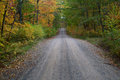Country dirt road a deserted in the is flanked by trees with colorful autumn leaves in eastern pennsylvania Stock Photo